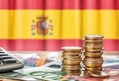 Euro banknotes and coins in front of the national flag of Spain stock photos