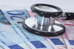 Euro banknotes, coins and stethoscope Stock Photo