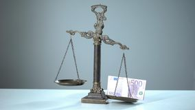 Euro banknotes dominates on scales, social inequality concept wealth and poverty. Stock photo stock images