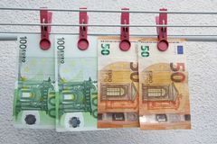Euro banknotes drying. Washed Euro paper bills. Drying euro on a string. stock images