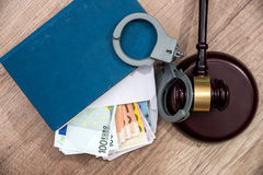 Euro banknotes in an envelope, handcuffs and hammer judges. The concept of corruption - euro banknotes in an envelope, handcuffs and hammer judges stock photo