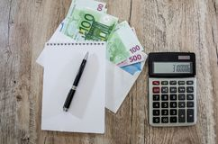Euro banknotes in envelope, notebook, pen and calculator. On the table stock photo