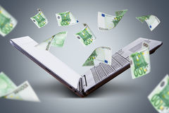 Euro Banknotes Flying around Laptop. Finance and earning concept, one hundred euro banknotes flying around laptop, internet, side view on dark background Royalty Free Stock Photo