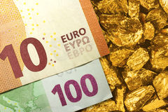 Euro banknotes on golden nuggets close up Royalty Free Stock Image