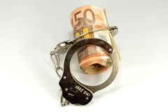 Euro banknotes and handcuffs Stock Images