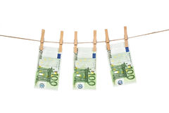 100 Euro banknotes hanging on clothesline on white background. Royalty Free Stock Photo