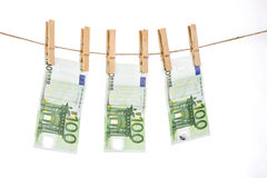 100 Euro banknotes hanging on clothesline on white background. Stock Photography