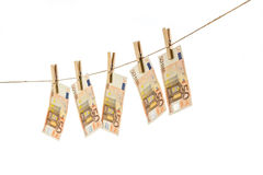 50 Euro banknotes hanging on clothesline on white background. Money laundering concept Stock Photos