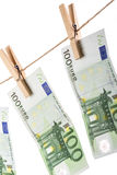 100 Euro banknotes hanging on clothesline on white background. Royalty Free Stock Photos