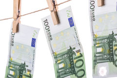 100 Euro banknotes hanging on clothesline on white background. Royalty Free Stock Images
