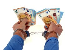 Handcuffed hands with banknotes on a white background. Euro banknotes held by handcuffed hands on a white background royalty free stock photography