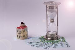 EURO banknotes and an hourglass and toy house on a light background . Time is money concept. EURO banknotes and an hourglass and toy house on a light background Stock Photography