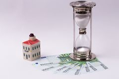 EURO banknotes and an hourglass and toy house on a white background. Time is money concept. Stock Image