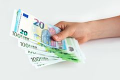 Free Euro Banknotes In Hand. 20 And 100 Euros On A White Isolated Background. Saving. European Union Stock Photo - 154355070