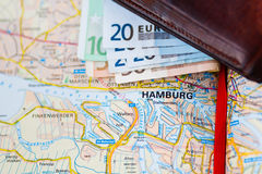 Euro banknotes inside wallet on a geographical map of Hamburg Royalty Free Stock Images