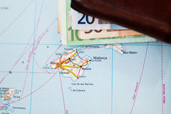 Euro banknotes inside wallet on a geographical map of Palma Stock Images