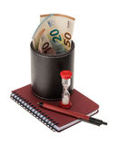 Euro banknotes in a leather holder, hourglass and writing materi Royalty Free Stock Photo
