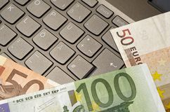 Euro banknotes lying on a keyboard with german layout. Three euro banknotes lying on a keyboard with german layout stock images