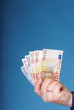 Euro banknotes in male hand. On blue background Stock Photo