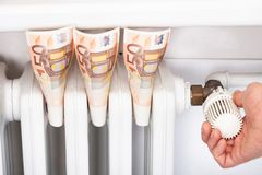 Euro banknotes by man adjusting thermostat Royalty Free Stock Images
