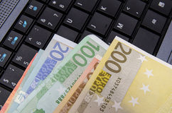 Euro banknotes over laptop keyboard Stock Images