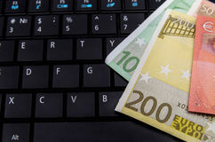 Euro banknotes over laptop keyboard Royalty Free Stock Photography