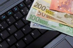 Euro banknotes over laptop keyboard Stock Image