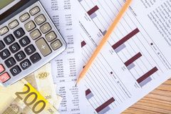 Euro Banknotes with Pencil and Calculator on Graph Chart. Finance concept, two hundred euro banknotes with pencil and calculator on graph chart analytics Royalty Free Stock Photography