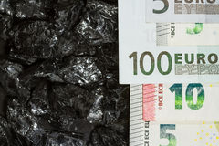 Euro banknotes on raw coal nuggets, bills on coal, power of money and ore royalty free stock photography
