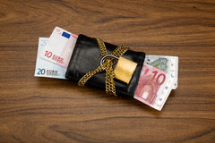 Euro banknotes secured in an locked black wallet. Euro banknotes in a black wallet locked with a golden chain and padlock on wooden walnut table Stock Images