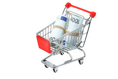 Euro banknotes in a shopping trolley cart. Rolls of Euro banknotes in a shopping trolley cart - studio shot with a white background Royalty Free Stock Image