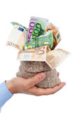Euro banknotes in small burlap sack. Held in businessman hand Royalty Free Stock Photography