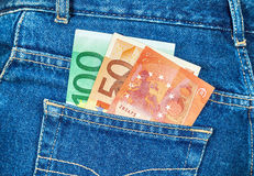 Euro banknotes sticking out of the back jeans pocket Stock Photo