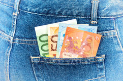 Euro banknotes sticking out of the blue jeans pocket Stock Image