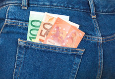 Euro banknotes sticking out of the blue jeans pocket. Money for Stock Photo