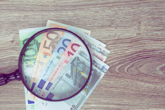 Euro banknotes under looking glass Royalty Free Stock Photos