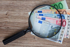 Euro banknotes under magnifying glass. Pile of euro banknotes under magnifying glass Stock Photography