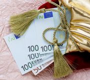 Euro banknotes wrapped in a gift on the background of crumpled paper. Euro banknotes, Packed in a gift bag with a Golden cord and tassel Stock Image