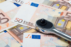 Euro banknotes and wrench Stock Photos