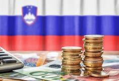 Euro banknoty i monety przed flagą państowową Slovenia obraz stock
