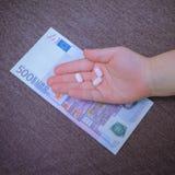 Euro banknoty i pastylki w dziecka ` s ręce Zdjęcia Stock