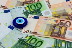Euro banknoty i zły oko Obrazy Stock