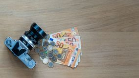 Euro banknoty, monety i kamera na lekkim drewnianym tle, obrazy royalty free