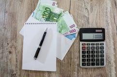 Euro banknoty w kopercie, notatniku, piórze i kalkulatorze, zdjęcie stock