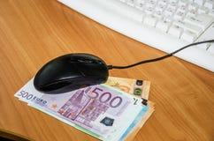 Euro banknoty z komputerową myszą i klawiaturą na drewnianym stole obrazy stock