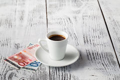 Euro bill and cup of coffee on wooden table. Payment, tip. Stock Images