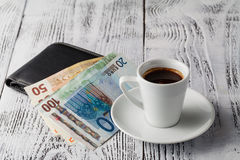 Euro bill and cup of coffee on wooden table. Payment, tip. Royalty Free Stock Photos