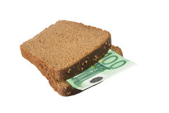 Euro bill between slices of bread. One-hundred euro bill between two slices of brown bread (isolated on white Royalty Free Stock Photo