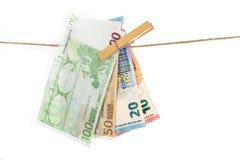 Euro billets de banque accrochant sur la corde à linge sur le fond blanc Photo stock