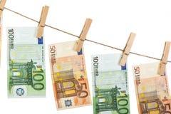 Euro billets de banque accrochant sur la corde à linge sur le fond blanc Image libre de droits